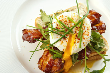 Bread with poached egg and bacon, top view