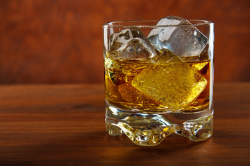 Whiskey on the rocks on wooden table