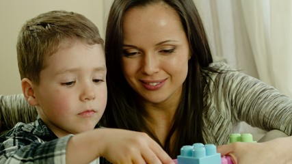 Happy young mother with her son on a sofa playing with building