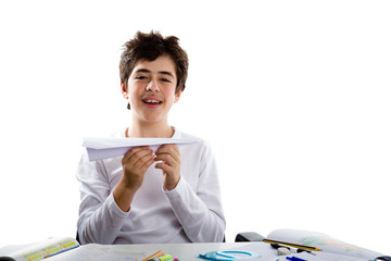 Latin boy playing with a paper airplane sitting in front of home