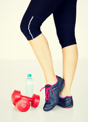 sporty woman legs with light red dumbbells