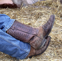 leather boots of lazy cowboy during the rest in the stable