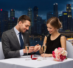 smiling couple with wedding ring at restaurant