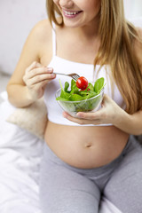 close up of pregnant woman eating salad from bowl