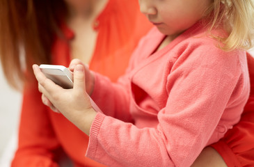 close up of woman and little girl with smartphone