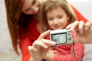 close up of happy mother and daughter with camera
