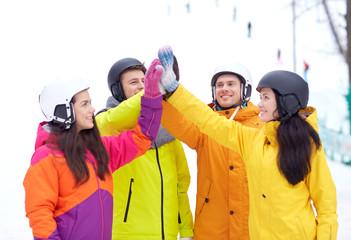 happy friends in helmets making high five