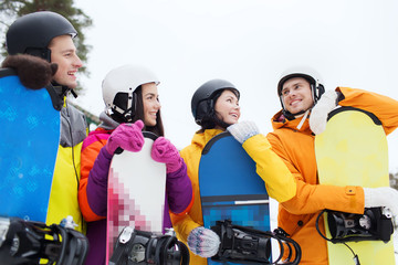 happy friends in helmets with snowboards talking
