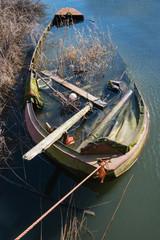Half sunken neglected steel rowboat