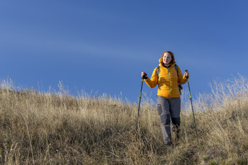 Female hiker walks downhill and enjoys warm sunlight