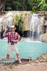 tourist posing beside waterfall