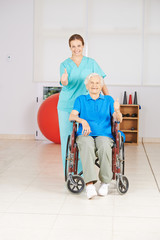 Seniorin im Rollstuhl hält Daumen hoch