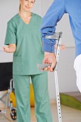 Physiotherapeut motiviert Mann mit Hand an Krücke
