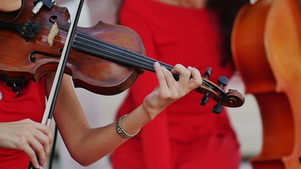 women in red dress musician playing violin close up shot slow