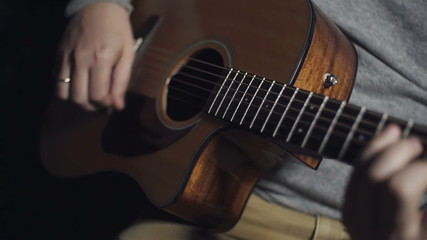 man playing guitar at black background slow motion
