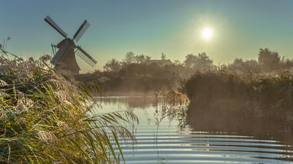 Dutch windmill in hazy wetland