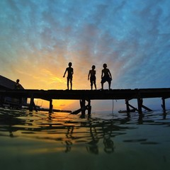 silhouette of young boys at bridge during sunset
