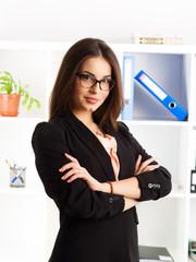 Portrait of pretty businessperson in eyeglasses posing in bureau