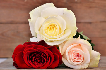 Three full-blown roses on wood background