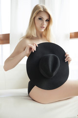 Young naked blonde posing with hat