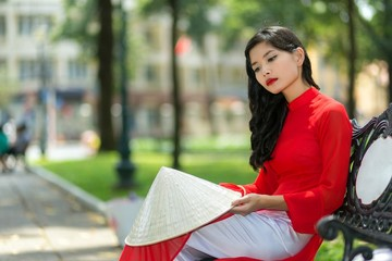 Sad young Vietnamese woman sitting on a bench