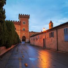 Bolgheri medieval village entrance and tower on sunset. Maremma,