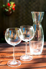 Two transparent shiny empty wineglasses and carafe in rays of su