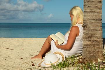 girl reading book at tropical beach