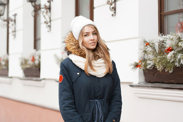 Beautiful girl in a knitted hat and jacket standing near the wal