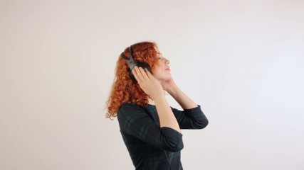 Young redhead girl with headphones on her head dancing
