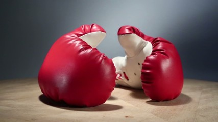 Red boxing gloves rotate on wooden table