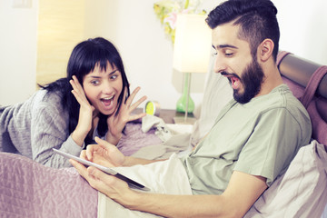 Surprised couple having won game online with tablet