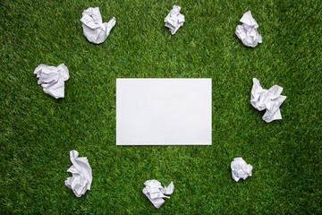 White sheets of paper with cramled sheets on the grass