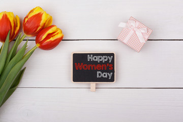 Blackboard with Happy Women's Day, bouquet of tulips and a gift