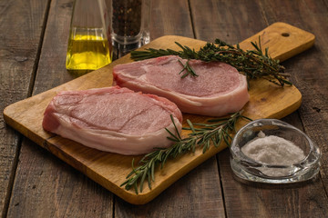 Raw pork steak with thyme and rosemary on a cutting board