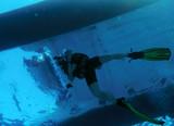 Diver Swimming under Catamaran