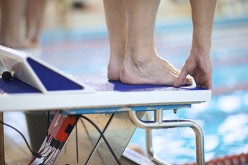 Feet of a swimmer on diving platform