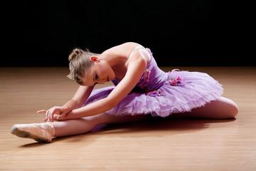 Teenage ballerina performing stretching exercises