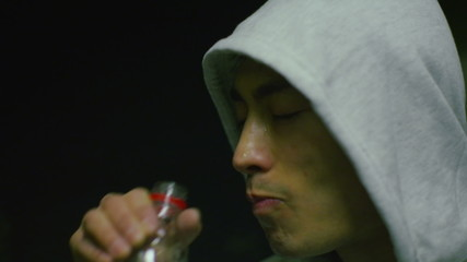 Hooded Asian man drinking bottled water after a workout