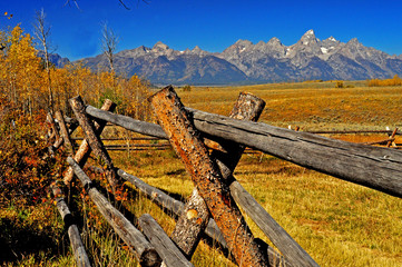 Wooden rail fence in shadow of Teton Mountains in fall.