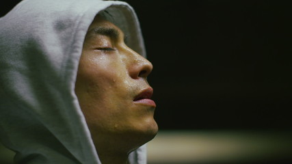 Hooded athlete getting his breath back