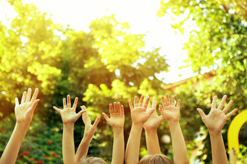 People hands up on sunny nature background