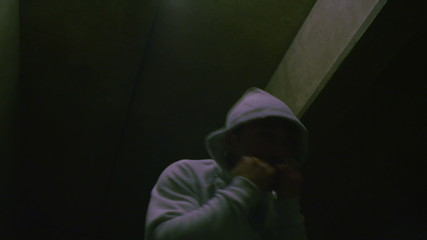 Hooded male boxer training at night