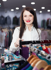 Smiling female buyer choosing clothes