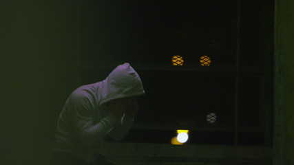Hooded male fighter training at night alone in slow motion
