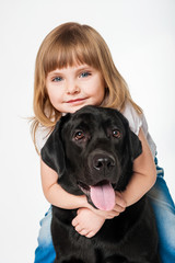 Beautiful girl hugging a black Labrador, on a gray background