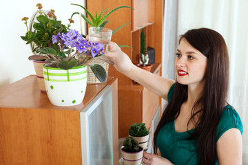 woman watering  flowers in pots at home
