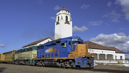 Train engine pulls its cars by the depot with blue sky