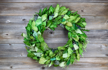 Seasonal green leaf wreath on rustic cedar wood