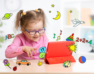 Kid with tablet computer in glasses. Early education.